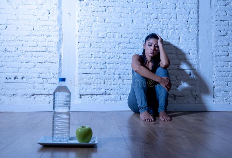 Depressed starving young woman on apple and water diet royalty free stock images