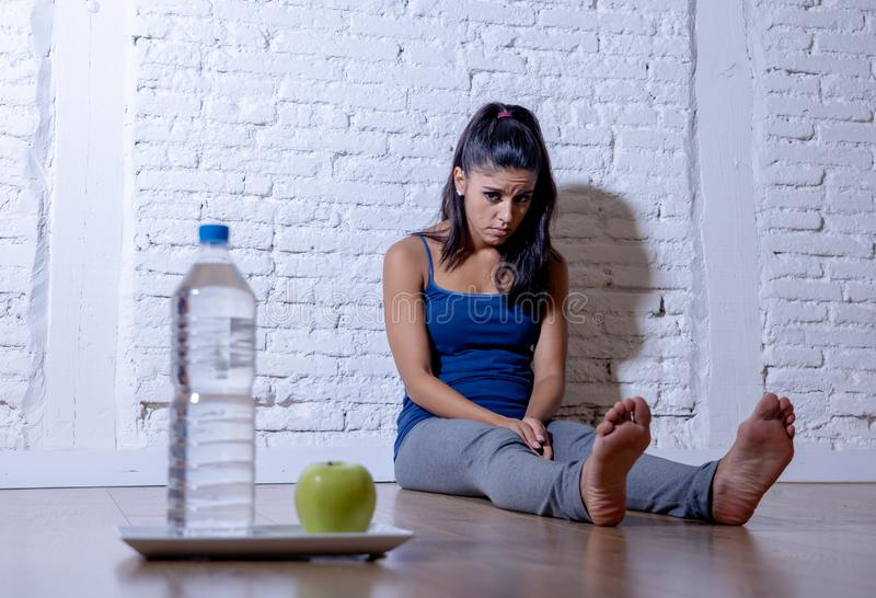 Depressed starving young woman on apple and water diet stock photography