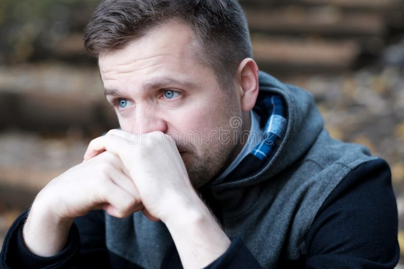 Desperate european man sitting alone on stairs outdoors in autumn. He broke up with his girlfriend. Migraine, education and overworking concept royalty free stock photos