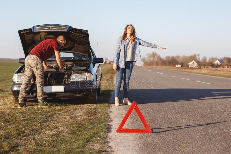 Desperate female stops vehicles on road as needs help, travel together with husband by car and have damage with engine, can`t solv royalty free stock photography