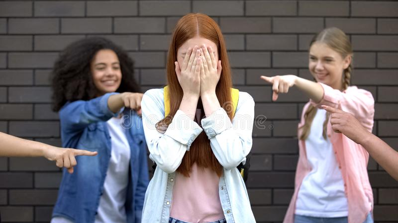 Desperate female teenager covering face by hands suffering school bullying royalty free stock images