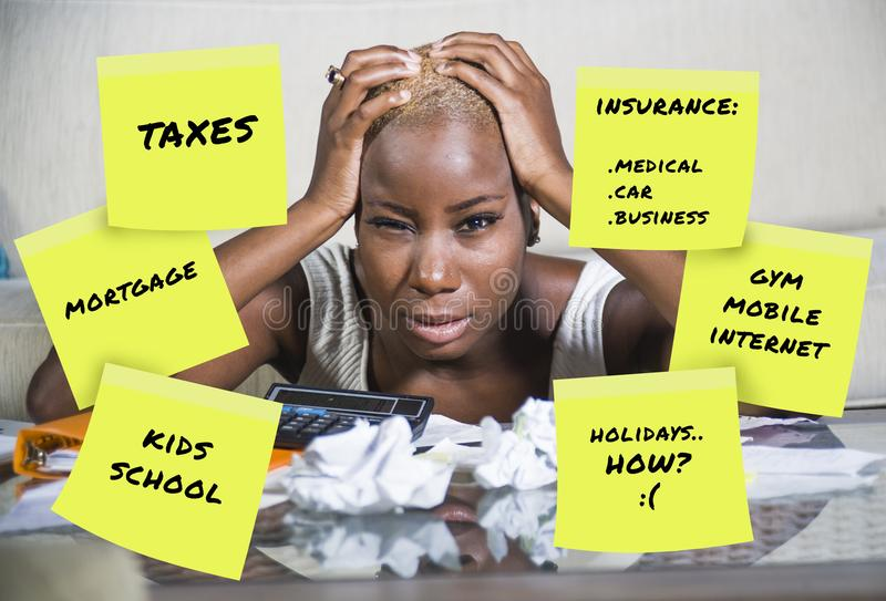 Desperate and frustrated black afro american woman domestic accounting worried about money paying taxes calculating expenses and p stock photo