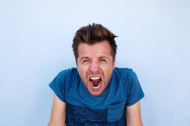Desperate furious raged man in blue shirt screaming loudly having his eyes full of anger. Concept og negative facial emotion stock images