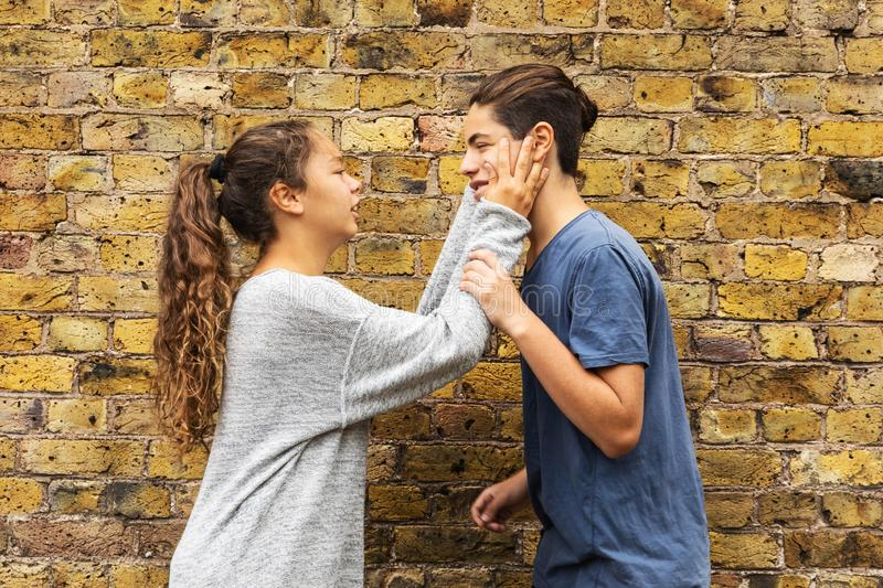 Desperate girl grabs the boy`s face with her hands. stock images