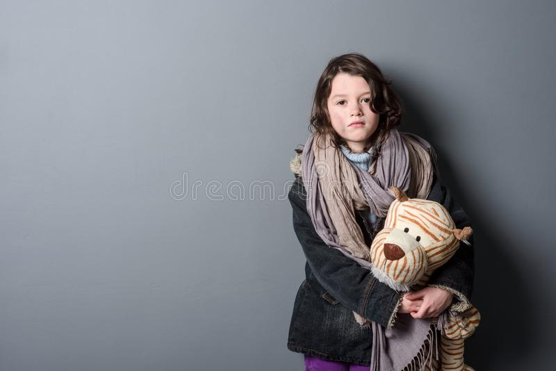 Desperate girl hugging old toy stock photo