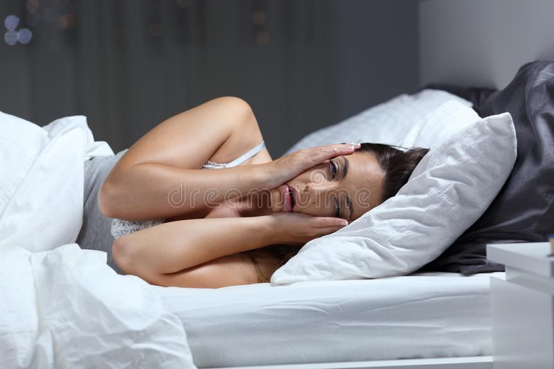 Desperate girl suffering insomnia trying to sleep. In a bed at home in the night stock photos