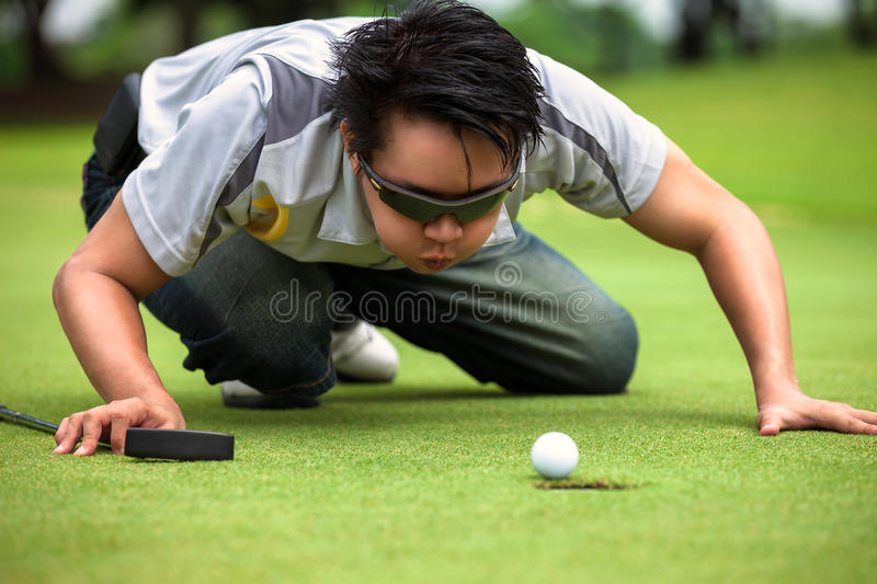 Desperate golfer. Blowing on golf ball to put in hole, Funny golfing cheat concept royalty free stock image