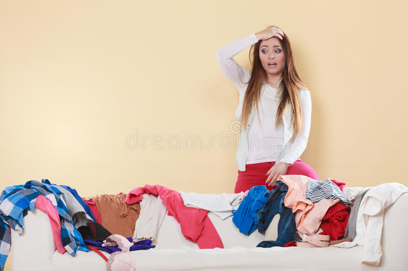 Desperate helpless woman in messy room home. Desperate helpless woman standing behind sofa couch in messy living room with hand on head. Young girl surrounded royalty free stock images