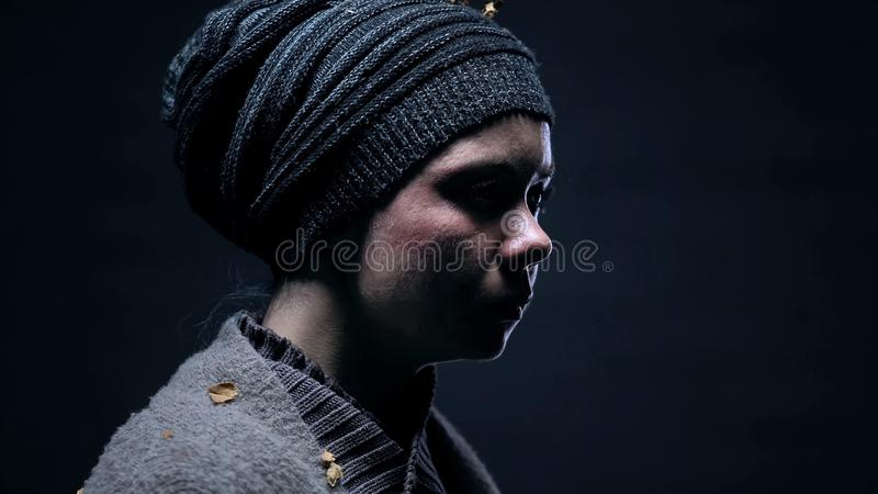 Desperate homeless female on dark background closeup, assault in family, poverty. Stock photo royalty free stock image