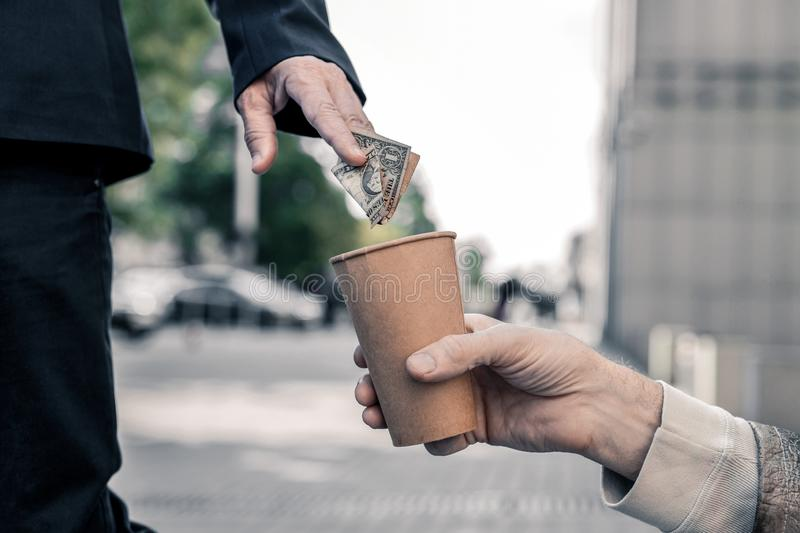 Rich business man stopping on street and compassionately sharing money. Desperate homeless. Rich business men stopping on street and compassionately sharing stock image