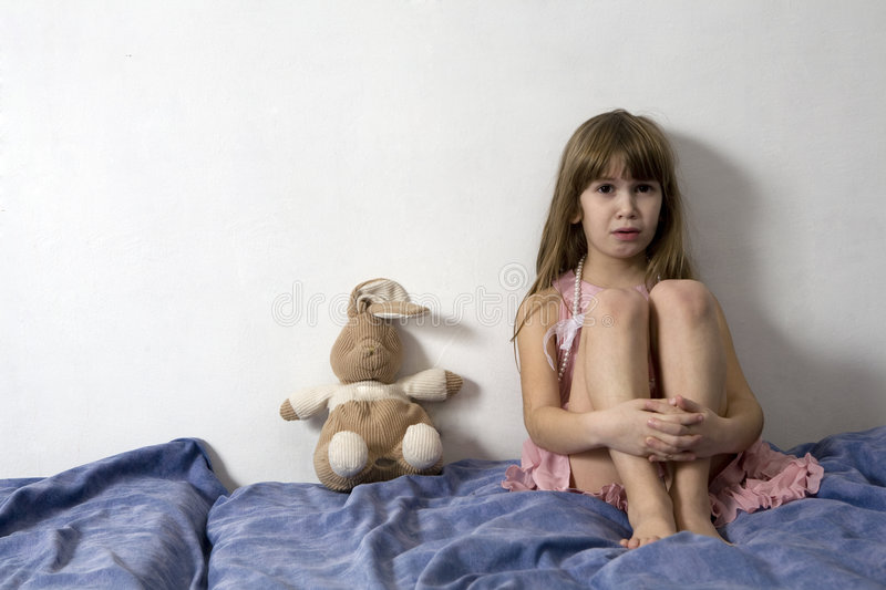 Desperate little girl is sitting on the sofa stock photography