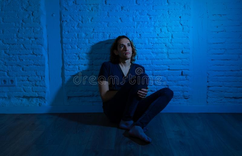 Desperate lonely teenager man suffering from depression sitting alone on floor at home. Devastated depressed millennial man crying sad feeling hurt suffering royalty free stock photography