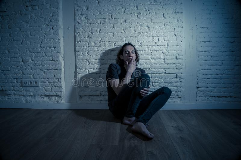 Desperate lonely teenager man suffering from depression sitting alone on floor at home. Devastated depressed millennial man crying sad feeling hurt suffering stock photos