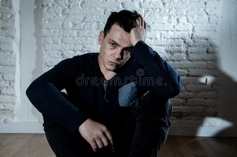 Desperate lonely unhappy caucasian man suffering from depression sitting alone on floor at home. Portrait of sad depressed young man crying devastated feeling royalty free stock photos