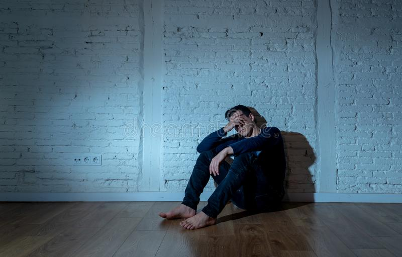 Desperate lonely unhappy caucasian man suffering from depression sitting alone on floor at home. Portrait of sad depressed young man crying devastated feeling royalty free stock photo
