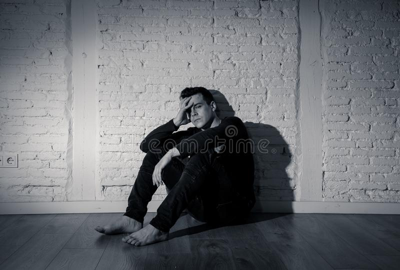 Desperate lonely unhappy caucasian man suffering from depression sitting alone on floor at home. Portrait of sad depressed young man crying devastated feeling stock images