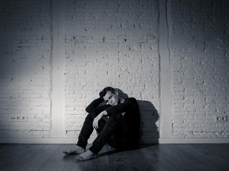 Desperate lonely unhappy caucasian man suffering from depression sitting alone on floor at home. Portrait of sad depressed young man crying devastated feeling stock photography