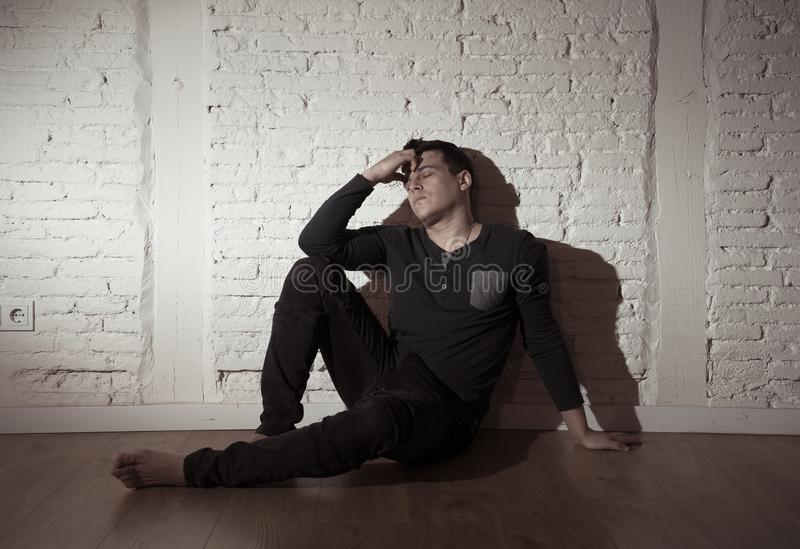 Desperate lonely unhappy caucasian man suffering from depression sitting alone on floor at home. Portrait of sad depressed young man crying devastated feeling royalty free stock photography