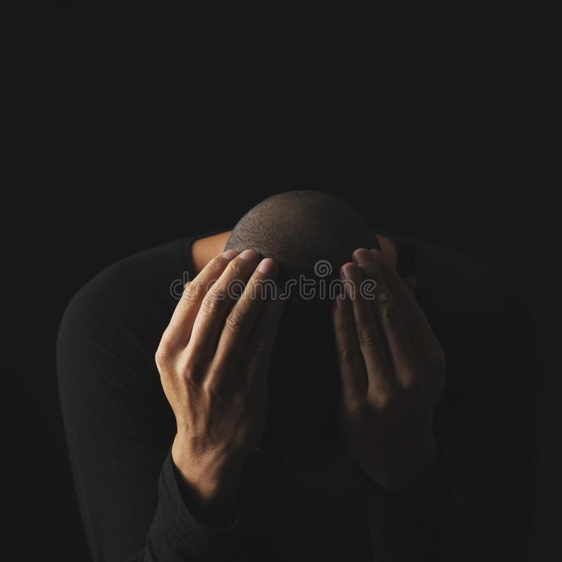 Desperate man with his hands in his head. Closeup of a desperate young caucasian man with his hands in his head, against a black background stock images