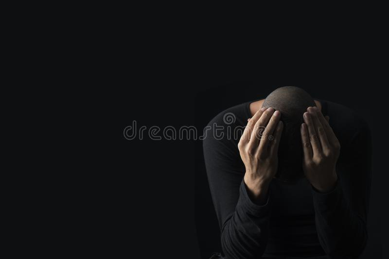 Desperate man with his hands in his head. Closeup of a desperate young caucasian man with his hands in his head, against a black background, with some blank royalty free stock image
