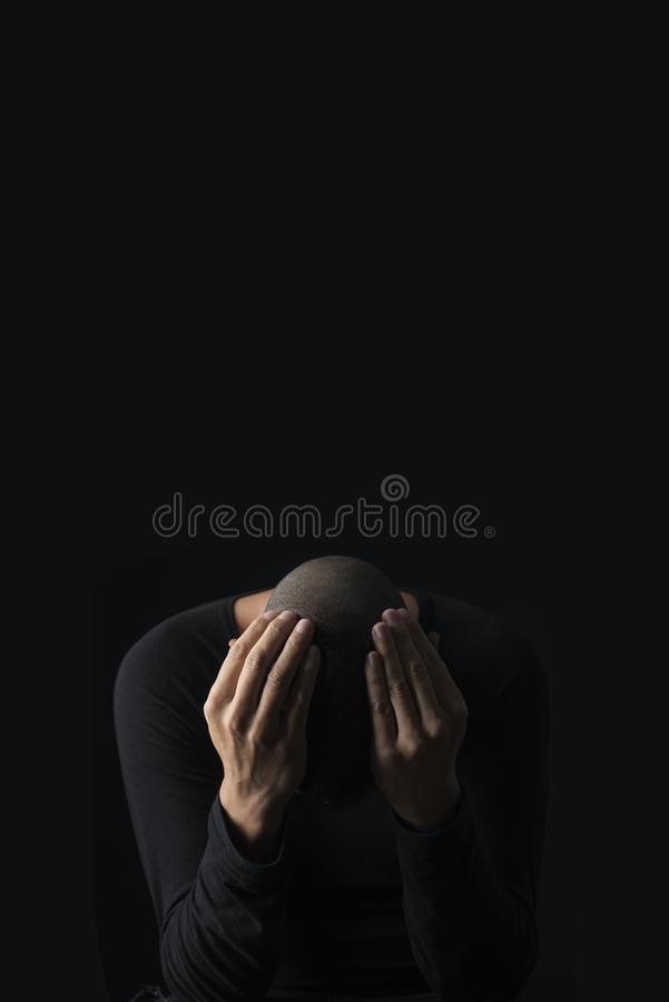 Desperate man with his hands in his head. Closeup of a desperate young caucasian man with his hands in his head, against a black background, with some blank stock photography