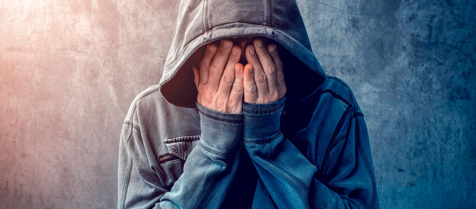 Desperate man in hooded jacket is crying stock photography