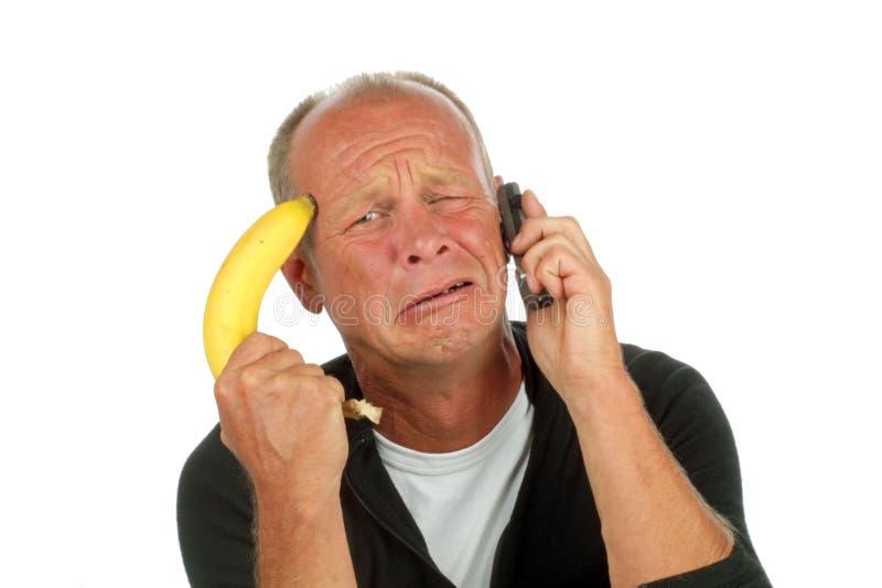 Desperate man phoning with banana gun stock images