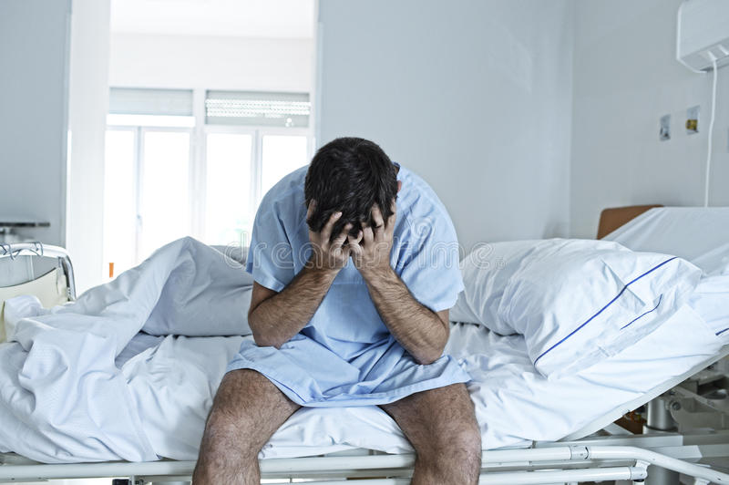 Desperate man sitting at hospital bed alone sad and devastated sick in clinic. Young desperate man sitting at hospital bed alone sad and devastated suffering royalty free stock photos