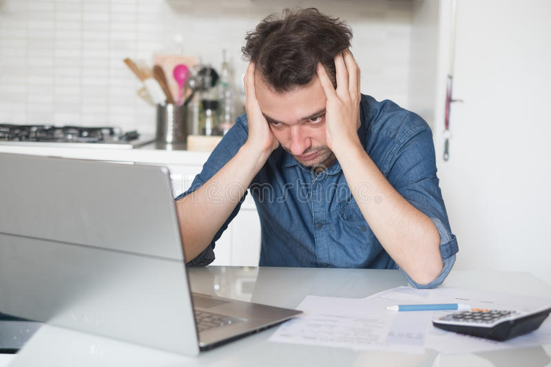 Desperate man trying to find solution for taxes and bills. Desperate man trying to find a solution for taxes and debts royalty free stock images