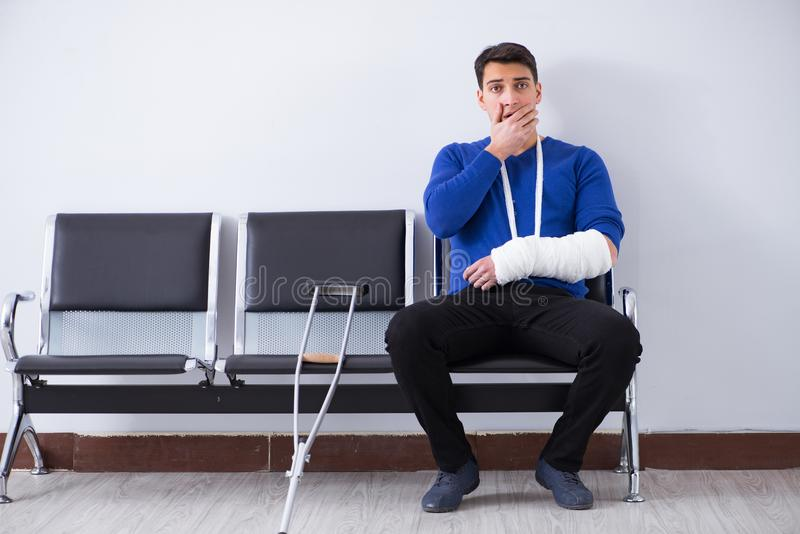 Desperate man waiting for his appointment in hospital with broke stock photography
