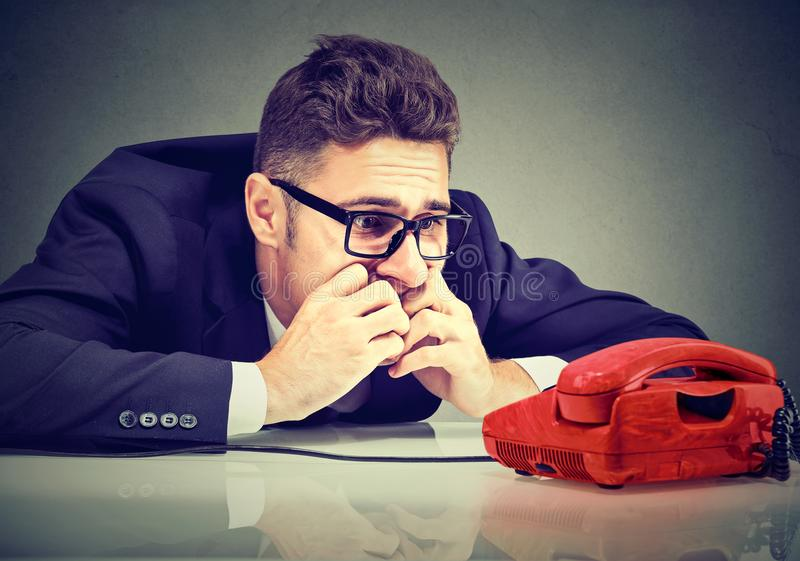 Desperate business man waiting for someone to call him. Desperate man waiting for someone important to call him on the phone royalty free stock image