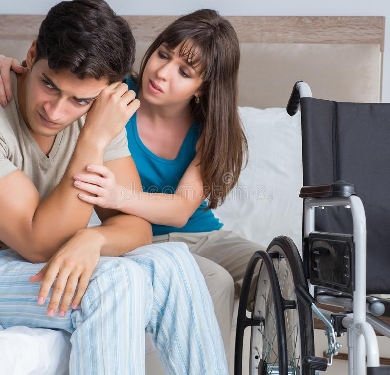 Desperate man on wheelchair with his sad wife. The desperate men on wheelchair with his sad wife stock photos