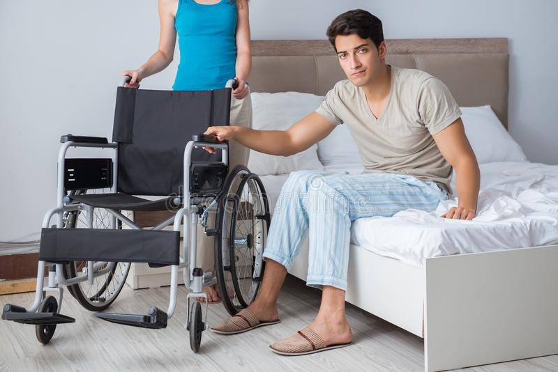 The desperate man on wheelchair with his sad wife. Desperate men on wheelchair with his sad wife stock image