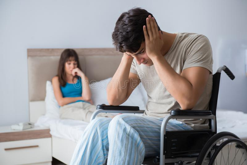 The desperate man on wheelchair with his sad wife. Desperate men on wheelchair with his sad wife stock images