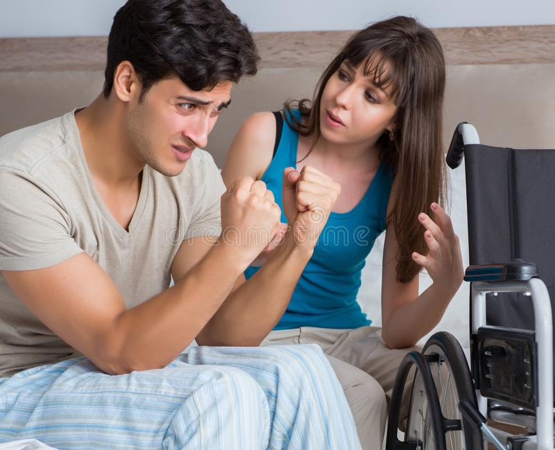 Desperate man on wheelchair with his sad wife. The desperate men on wheelchair with his sad wife royalty free stock photo