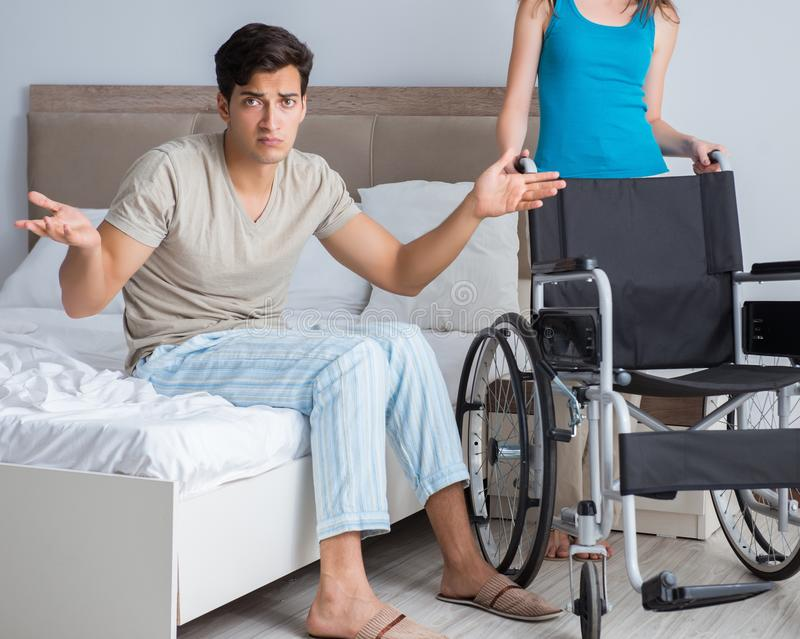 Desperate man on wheelchair with his sad wife. The desperate men on wheelchair with his sad wife royalty free stock images