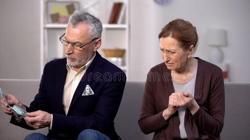 Desperate needy female looking at wealthy gentleman counting dollars, poverty. Stock photo stock photo