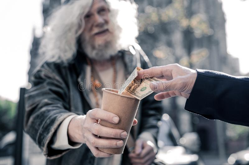 Grey-haired homeless man carrying cardboard cup and begging royalty free stock photography