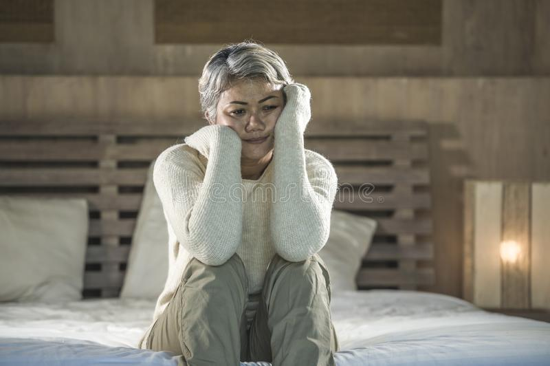 Dramatic lifestyle home portrait of attractive sad and depressed middle aged woman with grey hair on bed feeling upset suffering. Desperate 40s - 50s mature lady royalty free stock photography