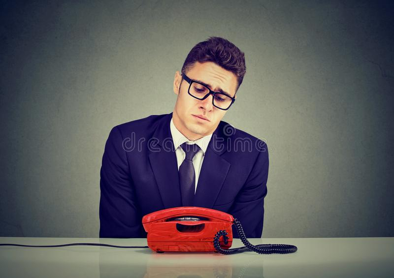 Desperate sad young business man waiting for someone to call him stock photos