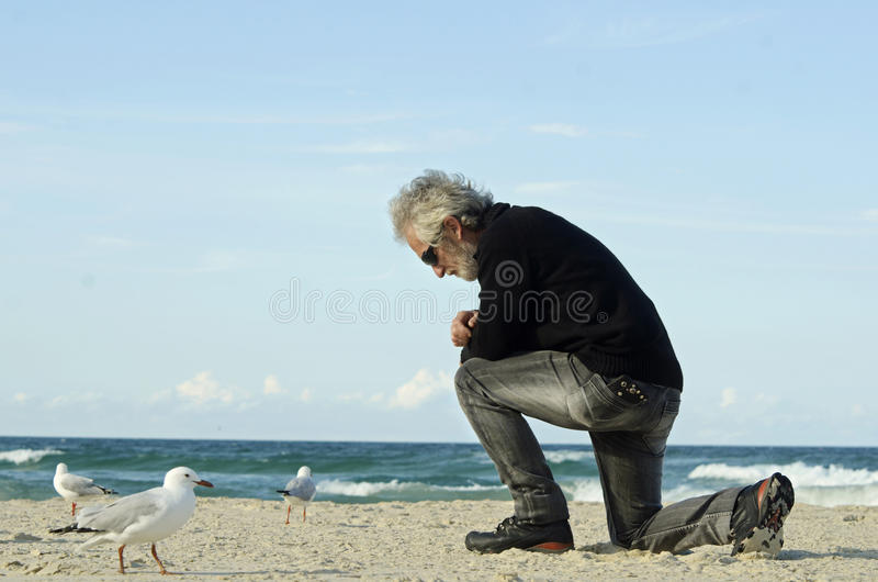 Desperate sad lonely man praying alone on ocean beach stock photography
