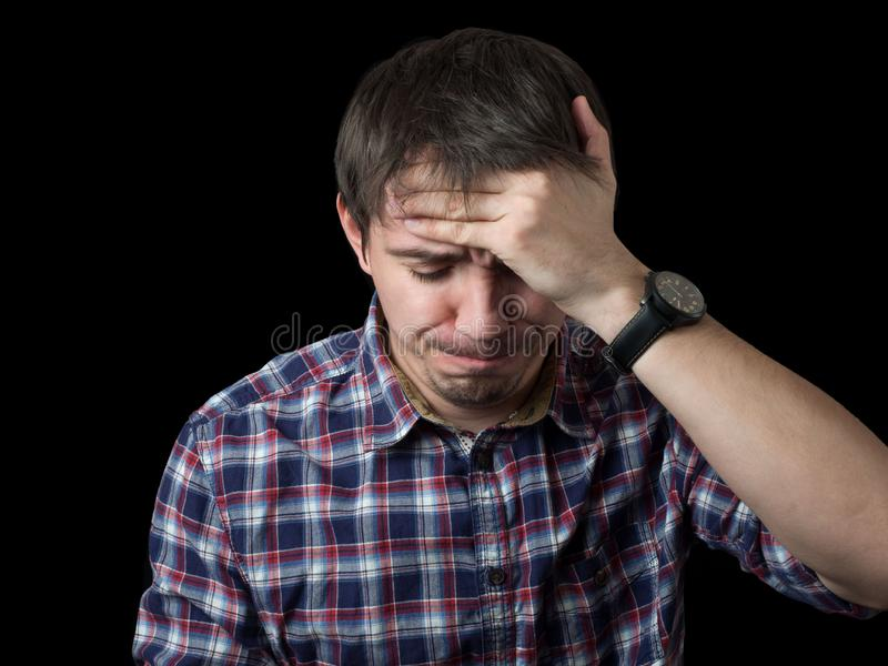 Desperate, sad, worried or upset young man with his eyes closed holding his head. stock photography