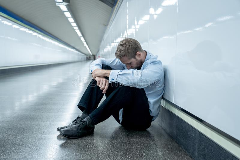 Sad young businessman jobless suffering from depression sitting depressed on ground street subway. Desperate sad young businessman suffering emotional pain grief royalty free stock photography