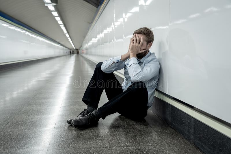 Sad young businessman jobless suffering from depression sitting depressed on ground street subway. Desperate sad young businessman suffering emotional pain grief royalty free stock images