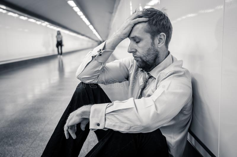 Desperate sad young businessman suffering emotional pain grief and deep depression sitting alone in tunnel subway in Stress life. Style Work problems failure royalty free stock photos