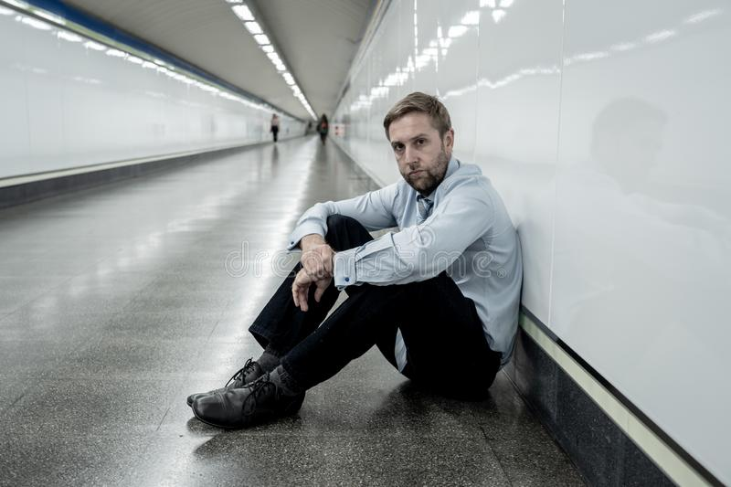 Desperate sad young businessman suffering emotional pain grief and deep depression sitting alone in tunnel subway in Stress life. Style Work problems failure stock images