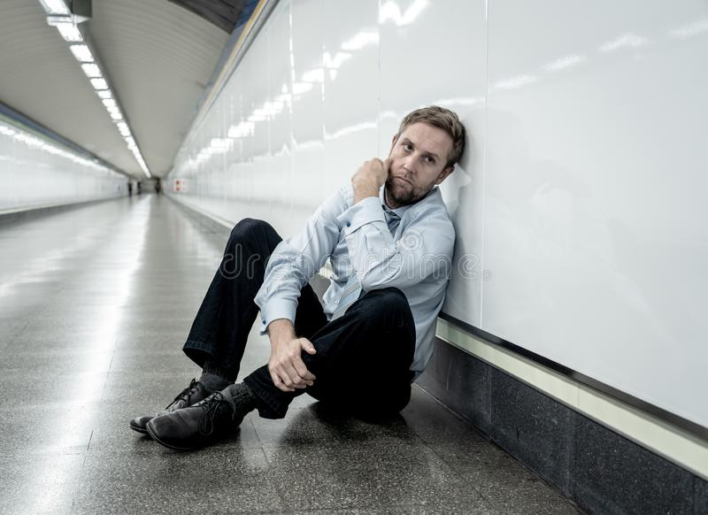 Desperate sad young businessman suffering emotional pain grief and deep depression sitting alone in tunnel subway in Stress life. Style Work problems failure royalty free stock photo