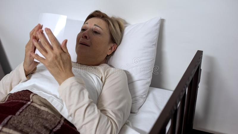 Desperate sick female lying in hospital bed, looking at family photo and crying royalty free stock photos