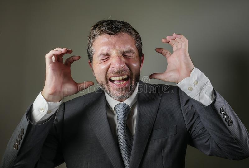 Stressed businessman screaming crazy frustrated and worried suffering depression problem and anxiety crisis on grey. Desperate and stressed businessman screaming stock image