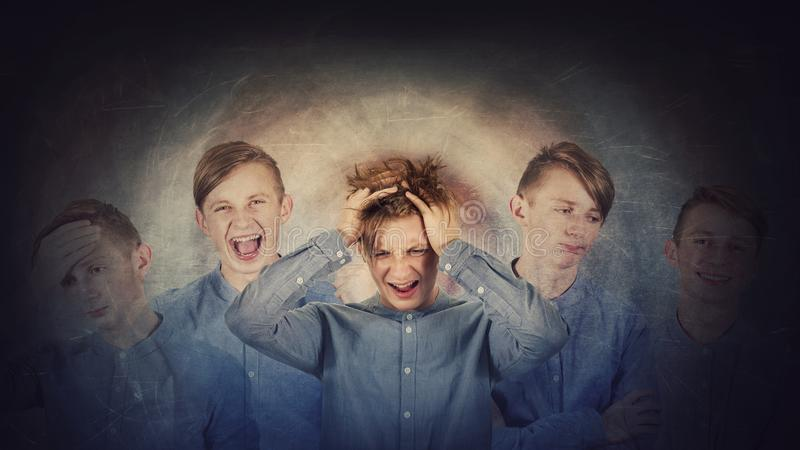 Desperate teenage boy, hands to head, suffer split emotions into different inner personalities. Multipolar mental health disorder stock photography
